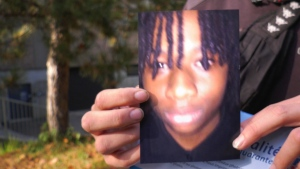 A friend holds up a photo of Jannai Dopwell-Bailey, 16, two days after he was stabbed outside his school. (Photo: Andrew Brennan)