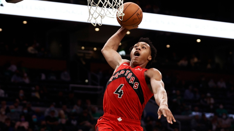 Toronto Raptors' Scottie Barnes (4) goes in for a dunk as Boston Celtics' Jayson Tatum (0) watches during the second half of an NBA preseason basketball game Saturday, Oct. 9, 2021, in Boston. (AP Photo/Winslow Townson)