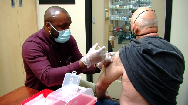 A Pharmacist giving a patient the flu shot.