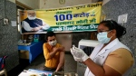 A health worker inoculates a man next to a banner thanking Prime Minister Narendra Modi for 1 billion doses of COVID-19 vaccine at a government hospital in New Delhi, India, Thursday, Oct. 21, 2021. (AP Photo/Manish Swarup)