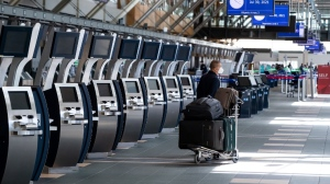 A traveller waits next to check-in kiosks not currently in use at Vancouver International Airport, in Richmond, B.C., on Friday, July 30, 2021. The federal government announced funding of up to $38.4 million for infrastructure projects at the airport as part of COVID-19 recovery efforts. THE CANADIAN PRESS/Darryl Dyck