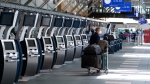 A traveller waits next to check-in kiosks not currently in use at Vancouver International Airport, in Richmond, B.C., on Friday, July 30, 2021. THE CANADIAN PRESS/Darryl Dyck