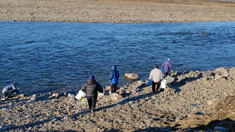 Qajuqturvik Community Food Centre staff members fill water jugs at the Sylvia Grinnell River, just outside Iqaluit, in an undated handout photo. The group has been delivering water to homes and organizations that may not have their own transportation, after the city warned last week its tap water was contaminated with fuel. (THE CANADIAN PRESS/HO-Rachel Blais)