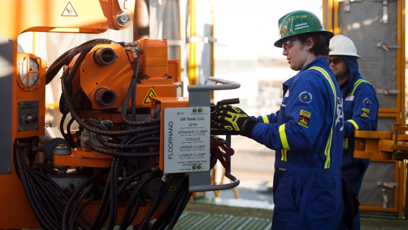 Blake Bernert ,left, learns from instructor instructor Clint Dyck during a training session to lay down drill pipe on a rig floor at Precision Drilling in Nisku, Alta., on Friday, January 20, 2016. (THE CANADIAN PRESS/Jason Franson)