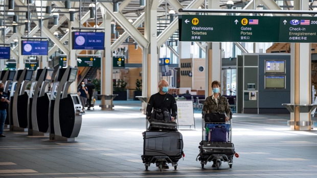 Travellers pushing luggage on carts walk through Vancouver International Airport, in Richmond, B.C., on Friday, July 30, 2021. THE CANADIAN PRESS/Darryl Dyck