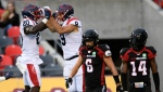 Montreal Alouettes wide receiver Jake Wieneke celebrates his touchdown with running back Jeshrun Antwi as Ottawa Redblacks defensive backs Antoine Pruneau and Abdul Kanneh walk away during first half CFL football action in Ottawa on Saturday, Oct. 16, 2021. (THE CANADIAN PRESS / Justin Tang)