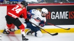 Canada's Natalie Spooner, left, checks Savannah Harmon, of the United States, during second period gold medal final IIHF Women's World Championship hockey action in Calgary, Tuesday, Aug. 31, 2021.THE CANADIAN PRESS/Jeff McIntosh