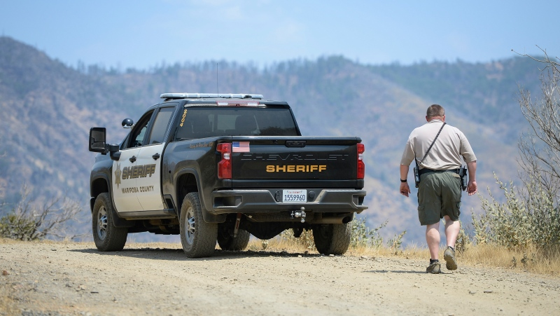 A Mariposa County deputy sheriff stands watch over a remote area northeast of the town of Mariposa, Calif., Aug. 18, 2021. (Craig Kohlruss/The Fresno Bee via AP)