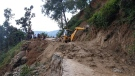 An earthmover helps clear a road affected by landslide after heavy rainfall in Dipayal Silgadhi, Nepal, Thursday, Oct. 21, 2021. (AP Photo/Laxmi Prasad Ngakhusi)