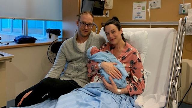 Proud parents Jason and Natalie Graham holding their newborn son Brooks in Sarnia, Ont. on Thursday, Oct. 21, 2021. (Reta Ismail / CTV News)
