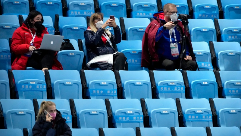 Team personnel wearing face masks to protect against COVID-19 watch the action at the ISU World Cup Short Track speed skating competition, a test event for the 2022 Winter Olympics, at the Capital Indoor Stadium in Beijing, Friday, Oct. 22, 2021. (AP Photo/Mark Schiefelbein)