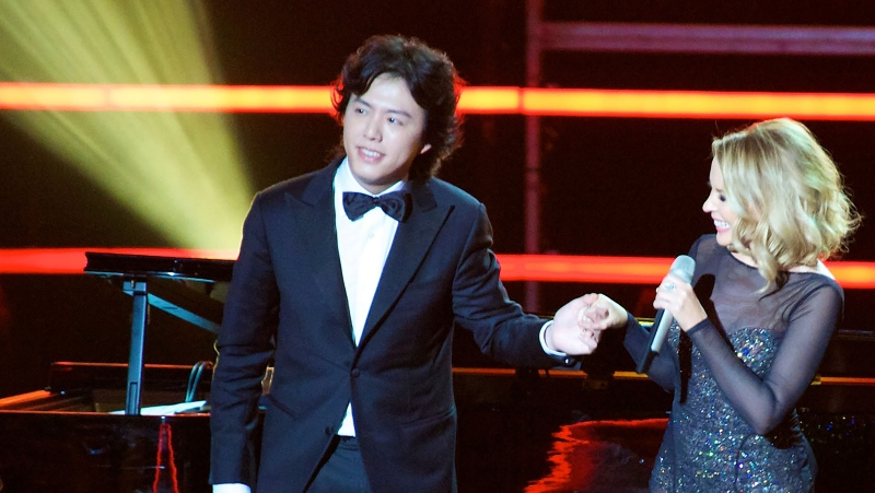Chinese pianist Li Yundi appears on stage with Australian singer Kylie Minogue during the 2011 Elite Model Look contest in Shanghai on Dec. 6, 2011.  (Chinatopix via AP)
