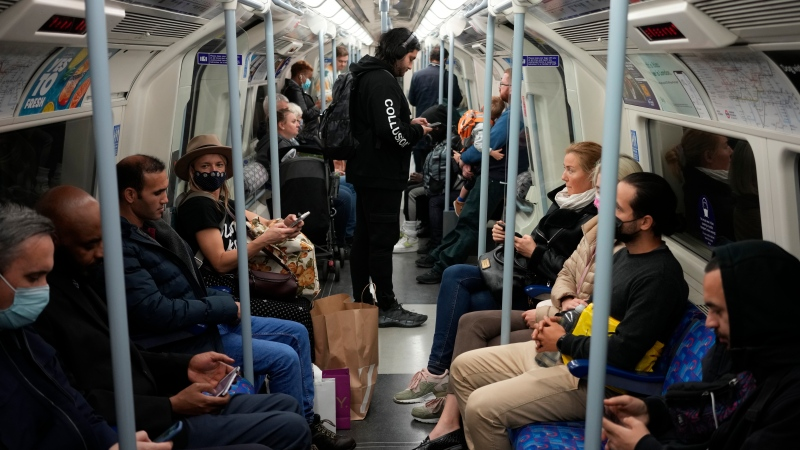 People travel on a London underground tube train on the Jubilee Line, where face coverings are required to be worn over people's mouths and noses, in London, Wednesday, Oct. 20, 2021. (AP Photo/Matt Dunham)