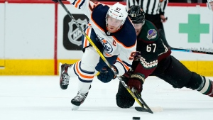 Edmonton Oilers center Connor McDavid (97) works against Arizona Coyotes left wing Lawson Crouse (67) for the puck during the second period of an NHL hockey game Thursday, Oct. 21, 2021, in Glendale, Ariz. (AP Photo/Ross D. Franklin)