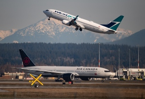An Air Canada flight departing for Toronto, bottom, taxis to a runway as a Westjet flight bound for Palm Springs takes off at Vancouver International Airport, in Richmond, B.C. (Photo: THE CANADIAN PRESS/Darryl Dyck)