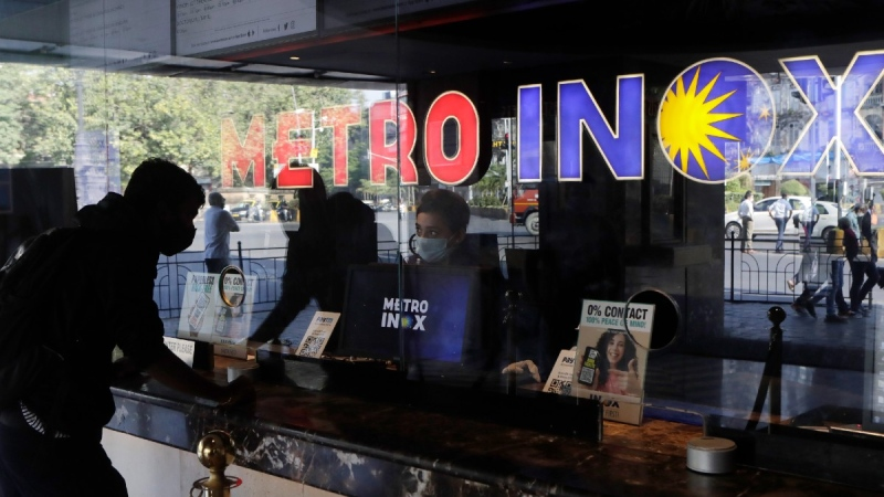 A man buys a ticket at a movie theatre in Mumbai, India, on Oct. 22, 2021. (Rajanish Kakade / AP)