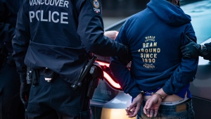 A man is handcuffed after being detained by Vancouver police officers in the Downtown Eastside of Vancouver, on Saturday, January 9, 2021. THE CANADIAN PRESS/Darryl Dyck