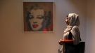 Fatemeh Rezaei, a retired teacher, stands next to Marilyn Monroe portrait by Andy Warhol at Tehran Museum of Contemporary Art, on Oct. 19, 2021. (Vahid Salemi / AP)