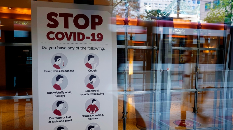 A sign reminds festival goers to monitor themselves for possible coronavirus symptoms in the entrance of the Princess of Wales Theatre on day one of the 2021 Toronto International Film Festival, Thursday, Sept. 9, 2021, in Toronto. (Chris Pizzello/Invision/AP)