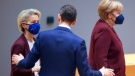 Poland's Prime Minister Mateusz Morawiecki, center, speaks with European Commission President Ursula von der Leyen, left, and German Chancellor Angela Merkel during a round table meeting at an EU summit in Brussels, Friday, Oct. 22, 2021. (AP Photo/Olivier Matthys, Pool)