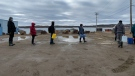 Residents line up to fill containers with potable water in Iqaluit, Oct. 14, 2021. THE CANADIAN PRESS/Emma Tranter