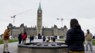 Visitors and tourists to Parliament Hill stand around the Centennial flame on Parliament Hill, in Ottawa, Friday, Oct. 22, 2021. A Parliament Hill memorial to Indigenous children who never returned from residential schools has been dismantled. (Adrian Wyld/THE CANADIAN PRESS)