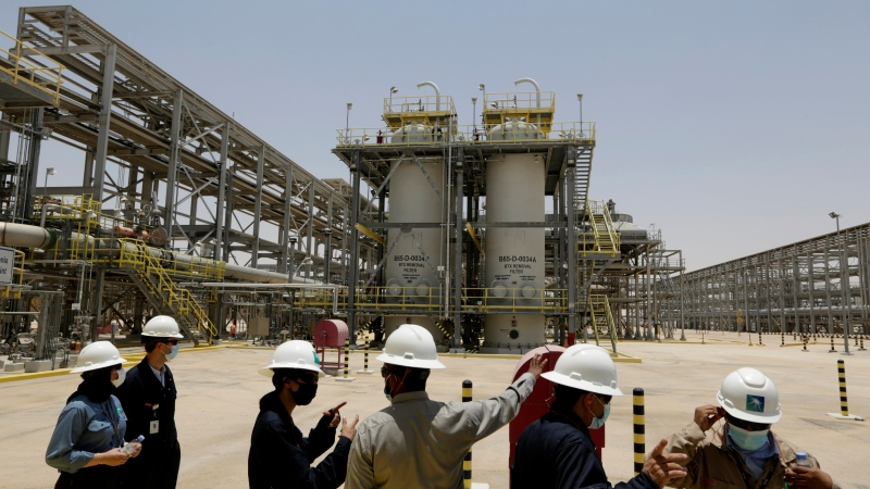 """Climate Saudi Arabia FILE - In this June 28, 2021, file photo, Saudi Aramco engineers and journalists look at the Hawiyah Natural Gas Liquids Recovery Plant in Hawiyah, in the Eastern Province of Saudi Arabia. One of the world's largest oil producers, Saudi Arabia, announced on Saturday, Oct. 23, it aims to reach """"net zero"""" greenhouse gas emissions by 2060, joining more than 100 countries in a global effort to try and curb man-made climate change. (AP Photo/Amr Nabil, File)"""