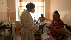 A medic speaks to a patient with coronavirus at an ICU of the city hospital in Rivne, Ukraine, Friday, Oct. 22, 2021.  (AP Photo/Evgeniy Maloletka)