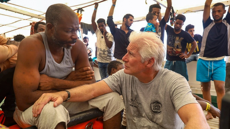 Actor Richard Gere, right, talks with migrants aboard the Open Arms Spanish humanitarian boat as it cruises in the Mediterranean Sea, Friday, Aug. 9, 2019. (Valerio Nicolosi/AP)