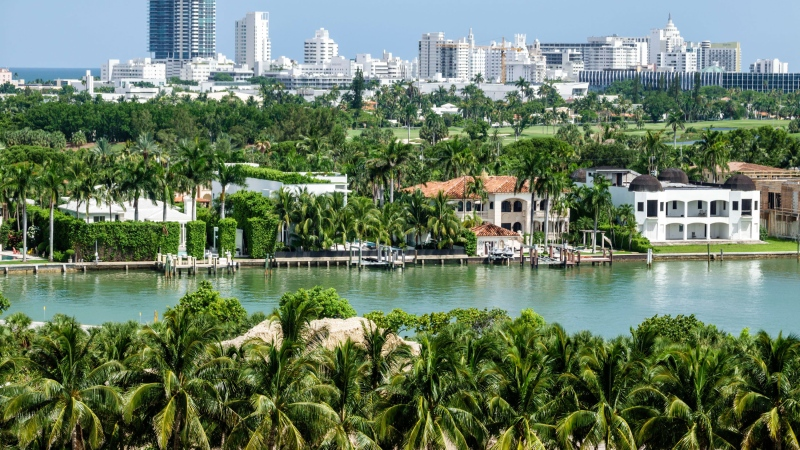 Miami Beach waterfront homes by Biscayne Bay surrounded by palms. (Jeff Greenberg/Universal Images Group/Getty Images/CNN)
