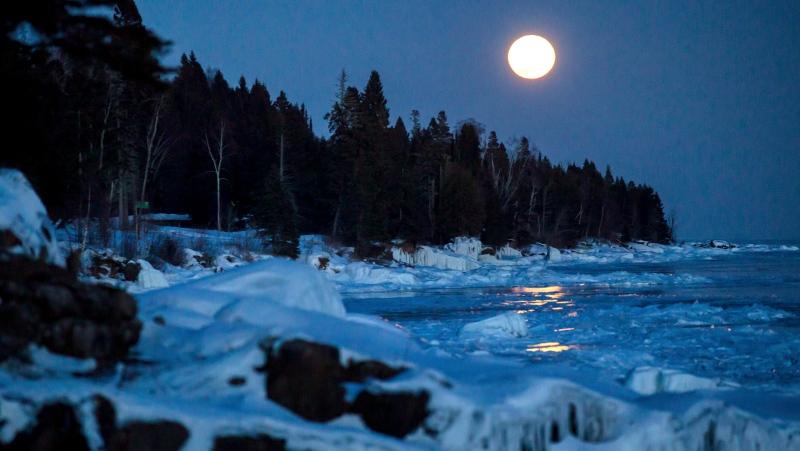 A super moon rises over the ice on the shore of Lake Superior, Tuesday, Feb. 19, 2019, in Lutsen, Minn. (AP Photo/Alex Brandon)