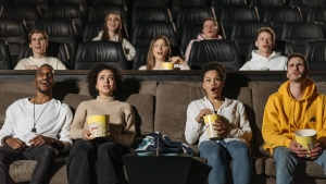People react while watching a film in a movie theatre. (Pexels)