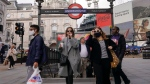 People wear face masks as they exit Piccadilly Circus underground station, in London, Oct. 19, 2021. (AP Photo/Alberto Pezzali)