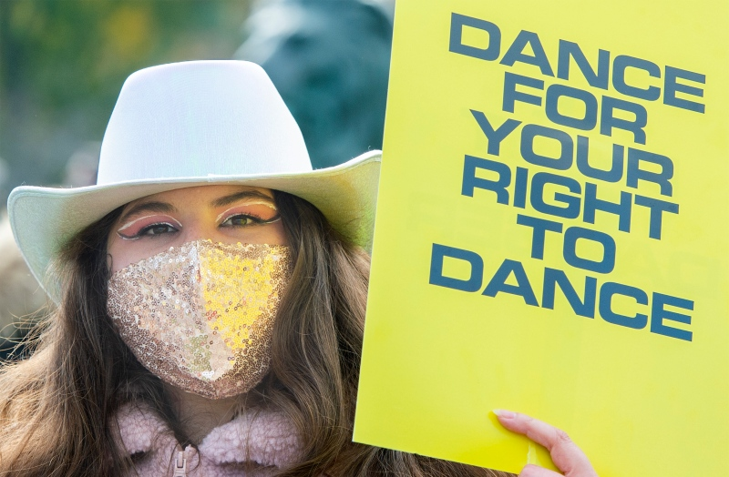 A woman holds up a sign during a protest in support of a return to dancing in venues in Montreal, Saturday, Oct. 23, 2021. Quebec and British Columbia are the only two provinces that continue to ban dancing in bars and nightclubs as part of their COVID-19 regulations. THE CANADIAN PRESS/Graham Hughes