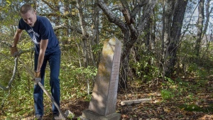 Steve Skafte, a photographer and writer based in Nova Scotia's Annapolis Valley, works to stabilize a grave marker in a small, long-abandoned cemetery in West Paradise, N.S. on Thursday, Oct. 21, 2021. Skafte established Abandoned Cemeteries of Nova Scotia, a Facebook group devoted to cataloguing burial sites that have been neglected or forgotten with the passage of time.  ANDREW VAUGHAN / THE CANADIAN PRESS