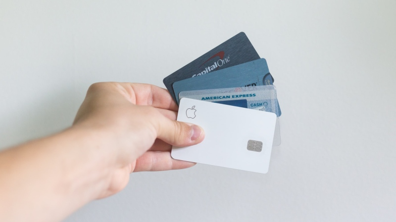 Stock image of person holding credit cards. (Unsplash, Avery Evans)