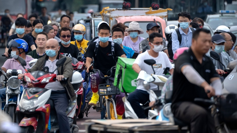 In this file photo dated Friday, July 2, 2021, people riding bicycles and scooters wait to cross an intersection during rush hour in Beijing. (AP Photo/Mark Schiefelbein, FILE)