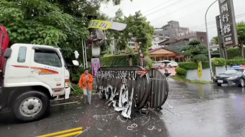 In this image from video, a person walks past a signboard which collapsed in Yilan County, Taiwan after an earthquake on Sunday, Oct. 24, 2021. (EBC via AP)