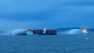 A photo of the M/V Zim Kingston, posted by the Canadian Coast Guard on Oct. 24, 2021, shows emergency vessels spraying water on the ship's hull. (Canadian Coast Guard/Twitter)