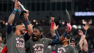 Atlanta Braves' Eddie Rosario holds the MVP trophy as he celebrates with Guillermo Heredia after winning Game 6 of baseball's National League Championship Series against the Los Angeles Dodgers Sunday, Oct. 24, 2021, in Atlanta. (AP Photo/Ashley Landis)