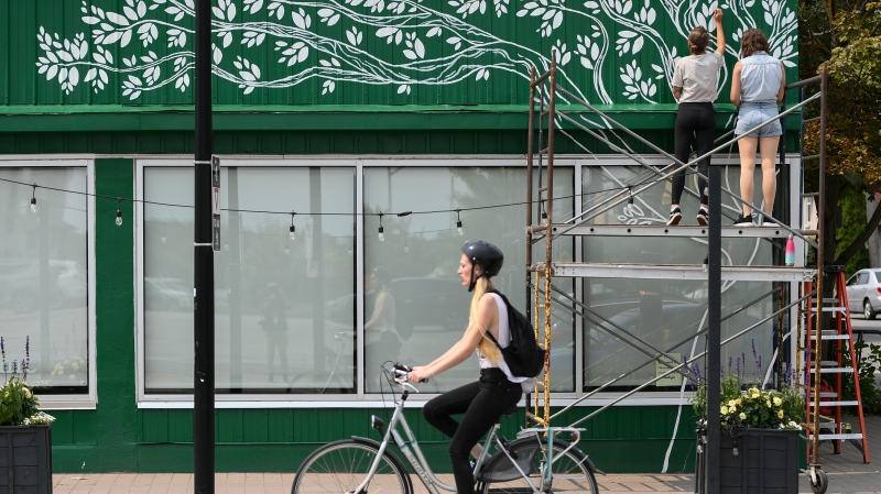 A cyclist rides past as Tori Lubbers and Emily Beckman, top right, paint a mural above the windows of the Green Door Restaurant in Ottawa, on Tuesday, Aug. 3, 2021. THE CANADIAN PRESS/Justin Tang