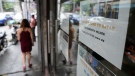 A woman walks beside a sign about hiring domestic helpers for the middle east outside an office in Manila, Philippines on Thursday, Oct. 21, 2021. (AP Photo/Aaron Favila)