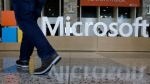 In this April 28, 2015, file photo, a man walks past a Microsoft sign set up for the Microsoft BUILD conference at Moscone Center in San Francisco. (AP Photo/Jeff Chiu, File)