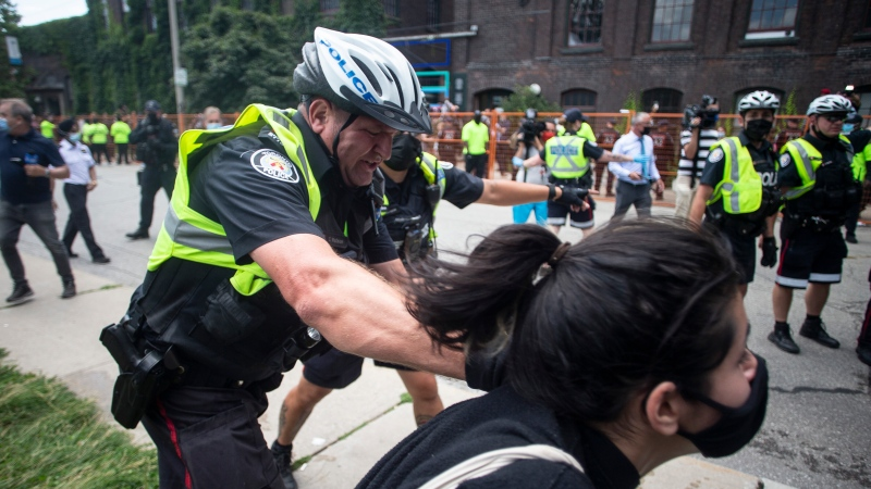 Toronto police remove an encampment supporter as they clear the Lamport Stadium Park encampment in Toronto on Wednesday July 21, 2021. THE CANADIAN PRESS/Chris Young