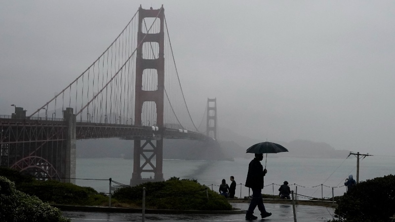 A pedestrian carries an umbrella while walking on a path in front of the Golden Gate Bridge in San Francisco, on Oct. 20, 2021. (Jeff Chiu / AP)