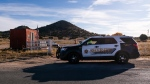 A Santa Fe County Sheriff's deputy briefly talks with a security guard at the entrance to the Bonanza Creek Ranch in Santa Fe, N.M., Monday, Oct. 25, 2021. (AP Photo/Jae C. Hong)