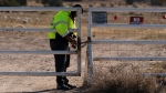A security guard manning the entrance to the Bonanza Creek Ranch film set locks the gate after turning away workers who came to pick up equipment in Santa Fe, N.M., Monday, Oct. 25, 2021. (AP Photo/Jae C. Hong)