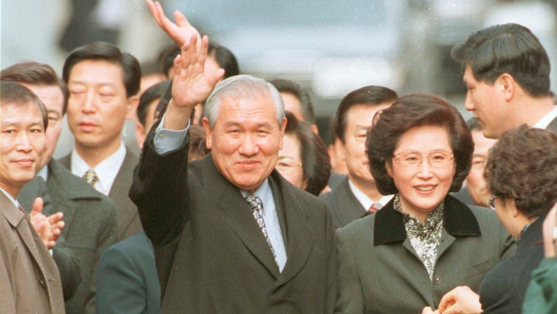 In this Dec. 22, 1997, file photo former South Korean President Roh Tae-woo, with his wife Kim Ok-sook standing beside him, waves to his supporters and neighbors upon arrival at his home after he was released from the Seoul prison in a special amnesty. (Yonhap via AP, Fiie)