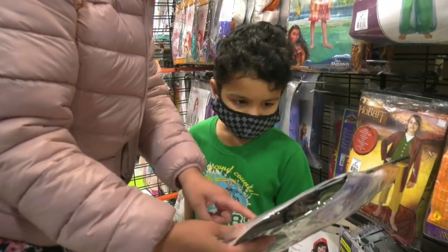A young boy looks at Halloween costumes with his mother at Party City in Barrie, Ont., on Monday, Oct. 25 (Chris Garry/CTV News)