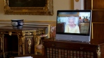 Queen Elizabeth II appears on a screen via videolink from Windsor Castle, where she is in residence, during a virtual audience at Buckingham Palace, London, Tuesday, Oct. 26, 2021. (Victoria Jones/Pool via AP)